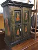 An Indian painted cupboard, the plain top above a pair of inset panel doors , each decorated with