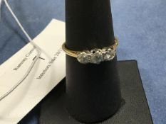 A three stone diamond ring on unmarked yellow metal band (O) (2.1g)