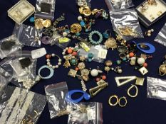 A bag containing a large quantity of earrings of various designs including drop earrings and stud