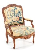 AN IMPORTANT REGENCE FAUTEUIL Walnut, profusely carved decoration with floral motifs. Lined with