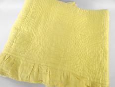 ANTIQUE WELSH QUILT in daffodil yellow, spiral design with larger centred motif, border skirt,