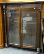 19TH CENTURY ROSEWOOD BOOKCASE having two glazed doors, column supports with carved acanthus