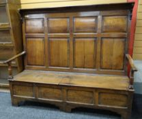 18TH CENTURY JOINED OAK BOX SETTLE, angled top with brackets above eight paneled tall back,