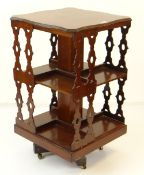 ANTIQUE MAHOGANY REVOLVING BOOKCASE TABLE with shaped top and gothic-style pierced sides, 47 x 47cms