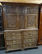 ANTIQUE OAK LINEN PRESS, paneled doors and front later carved with floral decoration on base woth