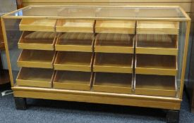 MID-CENTURY GLASS & LIGHTWOOD RETAILERS CABINET having a bank of sixteen tray-drawers, each with