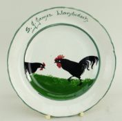 LLANELLY POTTERY TEA PLATE PAINTED WITH TWO STRUTTING BLACK COCKS inscribed to border S J James,