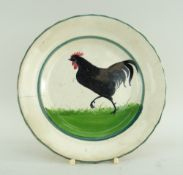 LLANELLY POTTERY SIDE-PLATE PAINTED WITH STRUTTING BLACK COCK on sponged grass within two green