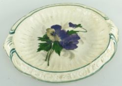 RARE LLANELLY POTTERY BREAD PLATE painted with pansies, the interior of fluted form, the sloped