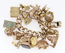 HEAVY 9CT GOLD FLAT CURB LINK CHARM BRACELET having an assortment of mainly 9ct gold charms