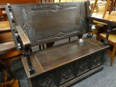 17TH CENTURY-STYLE CARVED OAK MONKS BENCH carved top and hinged box base, 122cms wide