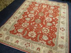 ORIENTAL RUG decorated with palmettes on a coral field, 240 x 300cms