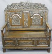 ANTIQUE STYLE OAK CARVED BOX SEAT SETTLE, the top rail with carved initials to the shield over a