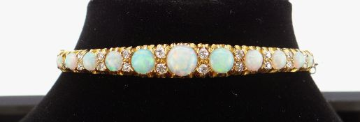 15CT GOLD OPAL & DIAMOND BANGLE, the eleven graduating opals alternating with graduating pairs of