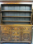 NORTH WALES ANGLESEY OAK DRESSER, CIRCA 1830, the wide boarded back three shelf rack with shaped