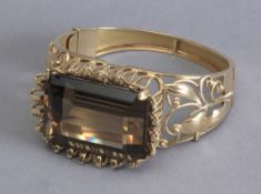 An 18k. yellow gold and a 101 ct. smoky quartz bangle