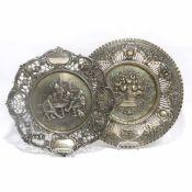 Zwei ZiertellerDeutsch, tlw. wohl Hanau. Silber. Die Fahnen durchbrochen gearbeitet mit reliefiertem