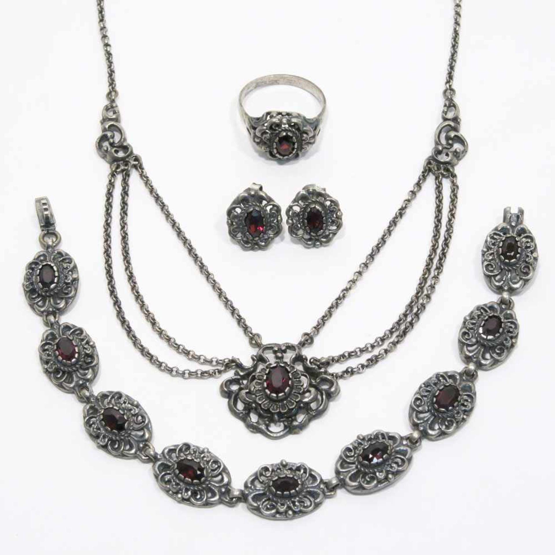 Parüre, 4tlg.Silber, Marken (800). Floraler, durchbrochener Dekor, mit ovalen Granaten besetzt. L.