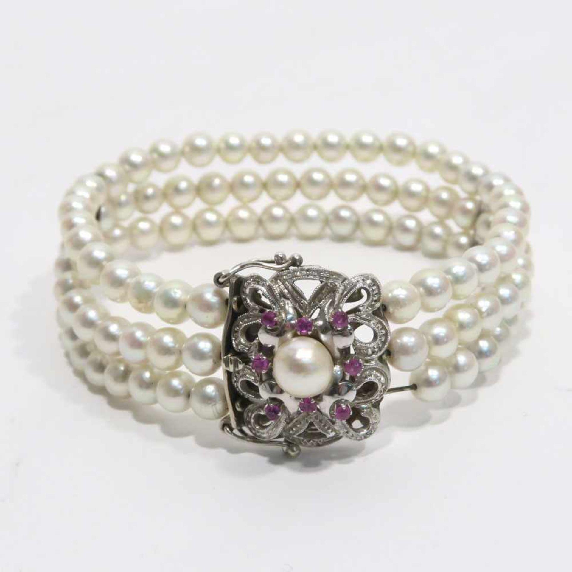 ZuchtperlenarmbandDreireihig. 18 K WG Schließe, Marke (750), mit Perle und acht Rubinen besetzt.