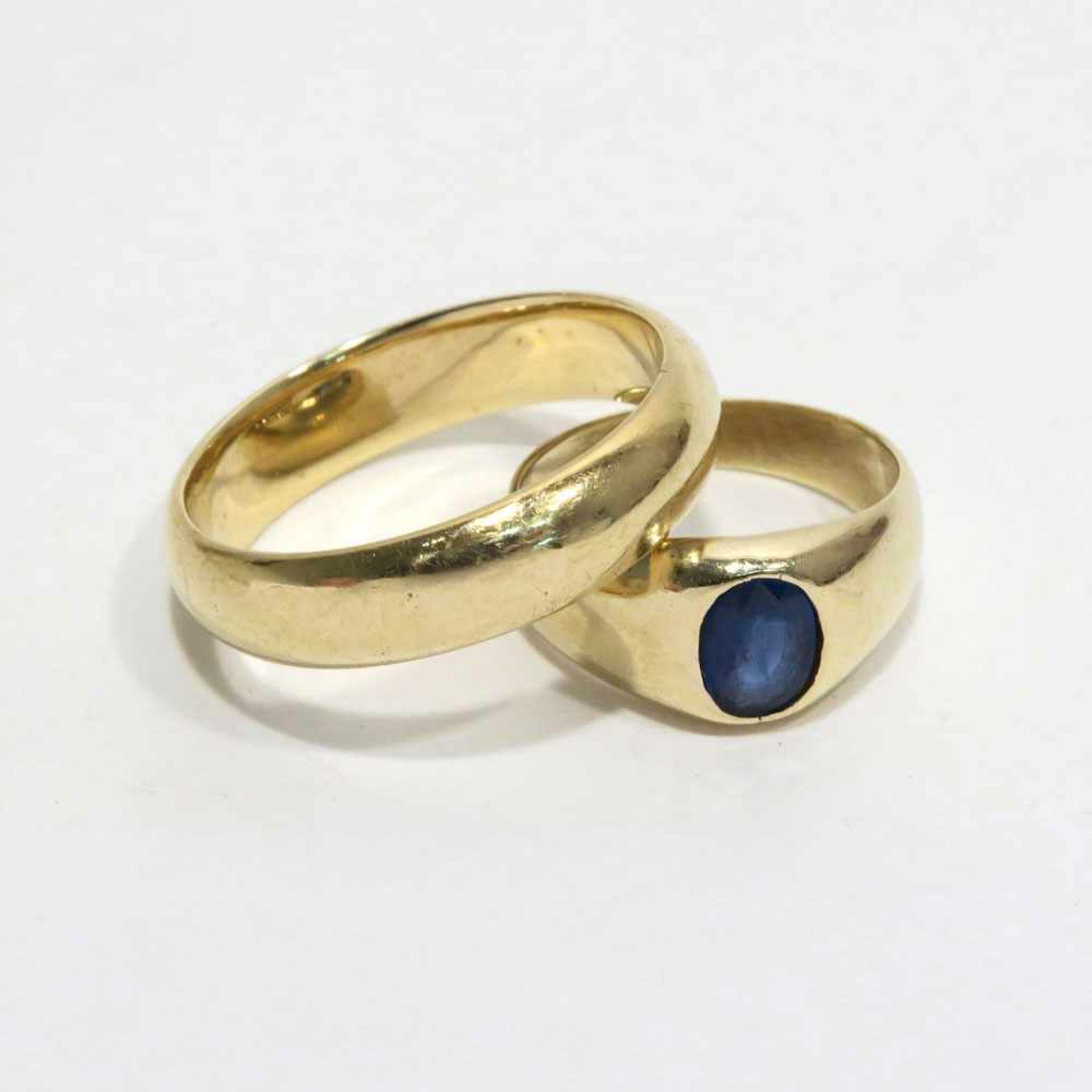 Zwei Ringe14 K GG, tlw. Marke (585, geprüft). Ehering bzw. Ring mit ovalem Saphir mittig besetzt.