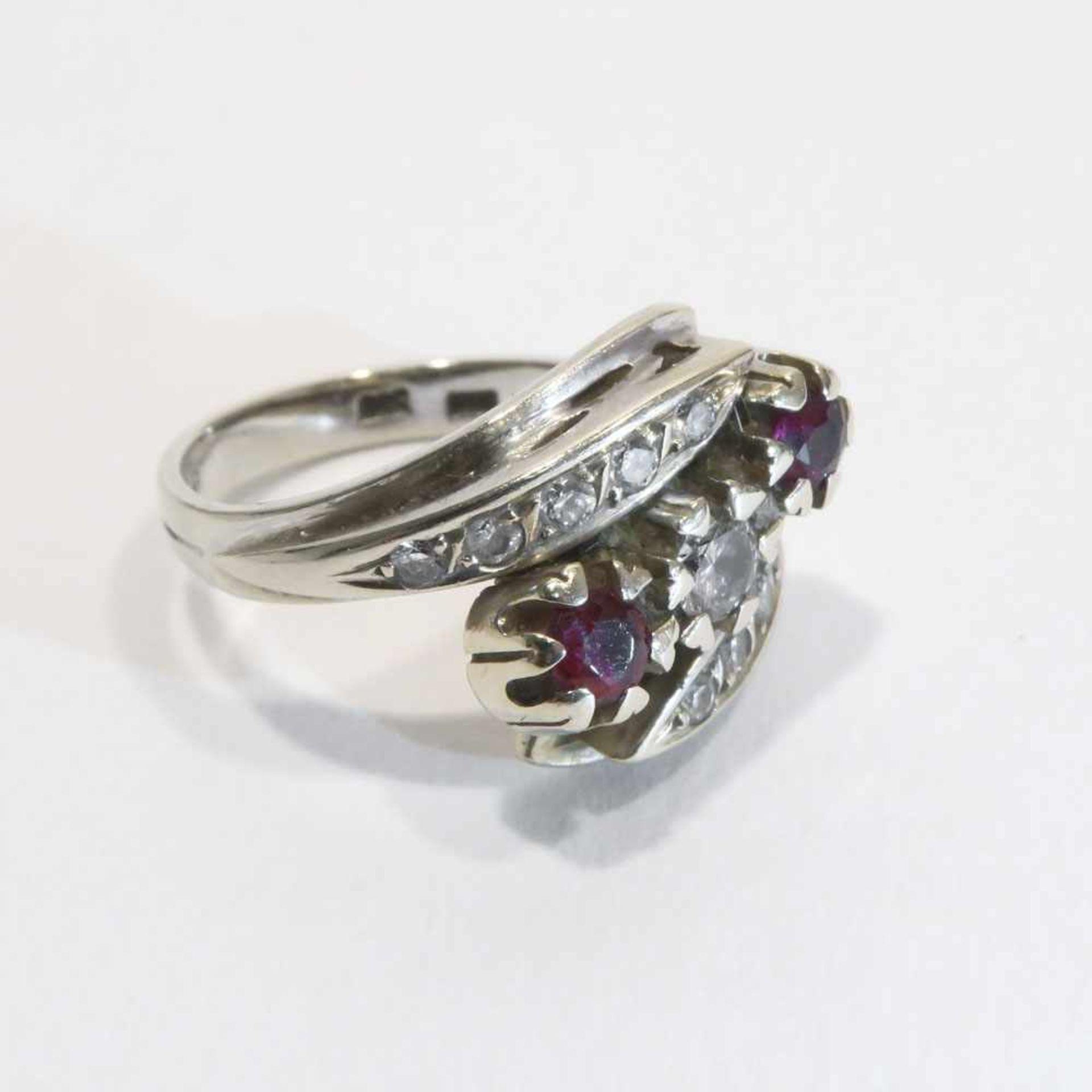 Ring14 K WG, Marke (585). Mit elf Brillanten, zus. ca. 0,2 ct, sowie zwei Rubinen, zus. ca. 0,2