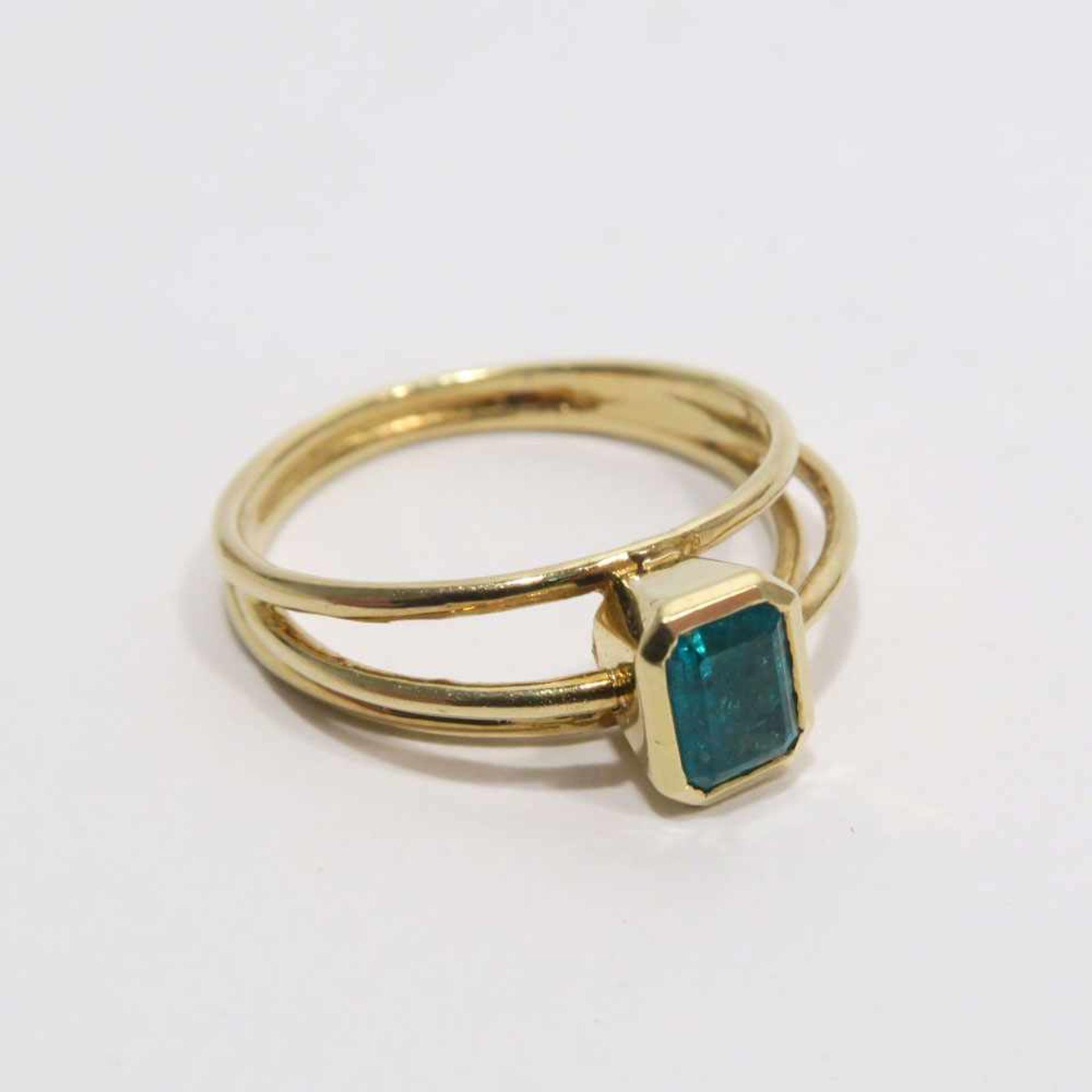 Ring18 K GG, (geprüft). Durchbrochene Ringschiene mittig besetzt mit rechteckigem Smaragd. Ringgröße