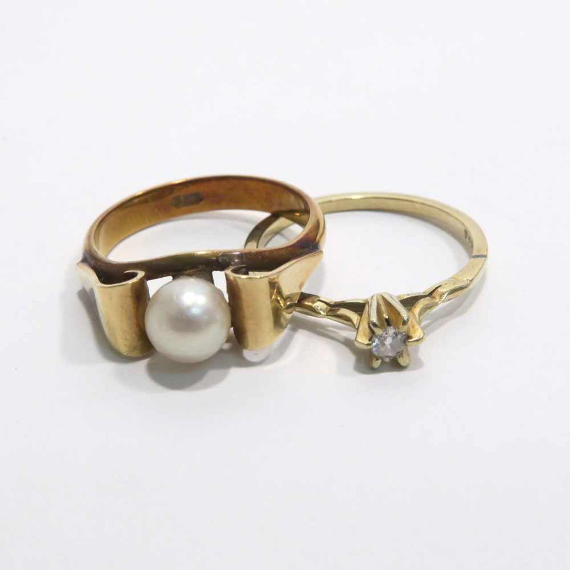 Zwei Ringe14 K GG, Marken (585). Mit einem Brillant bzw. einer Zuchtperle besetzt. Ringgröße 55 bzw.