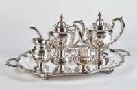 """Fünfteiliges Teeservice der Grafen Tolstoi St. Petersburg, um 1800 Ovales Tablett (L. 65 cm) auf vier Füßen und mit zwei Henkeln, die Fahne mit Faltenzügen und stark profiliertem Rand, zwei Kannen (H. 24 und 25,5 cm), eine runde Zuckerschale (H. 8,5 cm), ein Sahnegießer (H. 14,5 cm); Korpus akzentuiert durch breite Godronen, hochaufgewölbte Deckel mit Türmchenknauf; im Spiegel Vollwappen der Grafen Tolstoi, auf den Gefäßkörpern graviert kyrillisches Monogramm """"HT"""" (lat. NT) u..."""