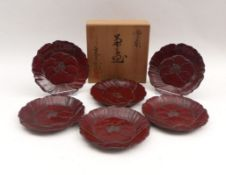 Sechs kleine Teller in BlütenformJapan, 20. Jh.Holz, oberseitig im Relief beschnitzt und rotbraun