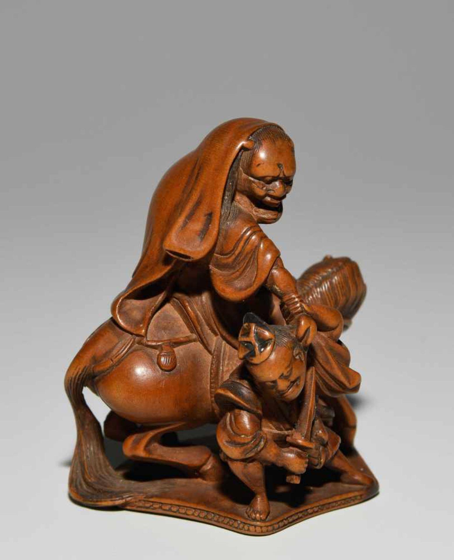 Los 1020 - *NetsukeJapan, 20.Jh. Buchsbaumholz. Oni auf Pferd reitend, im Kampf gegen einen Samurai. H 4,6 cm.