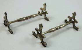 A silver pair of knife rests, Chester 1929, with scroll terminals, 9 cm, 2.5 oz.