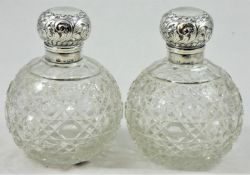 A pair of silver capped cut glass scent bottles, Birmingham 1904, the embossed hinged covers (one