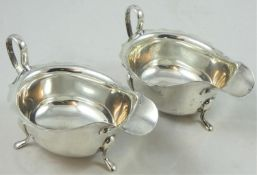 A pair of silver sauce boats, Sheffield 1932/33, with wavy edges, raised on three pad feet, 15 cm,