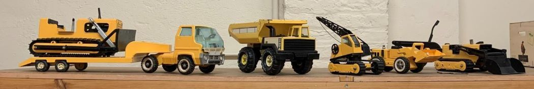 A collection of Tonka toys, including a transporter, truck, bulldozer, two diggers and a crane,