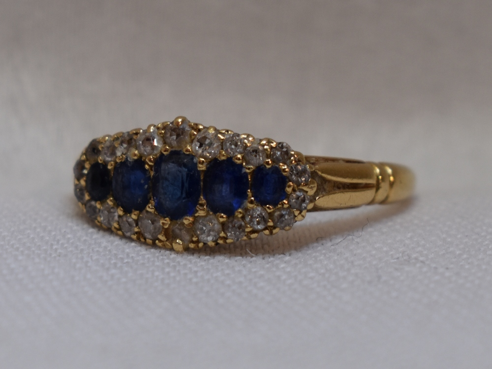 Lot 55 - A lady's dress ring having five graduated sapphires within a diamond chip border to moulded