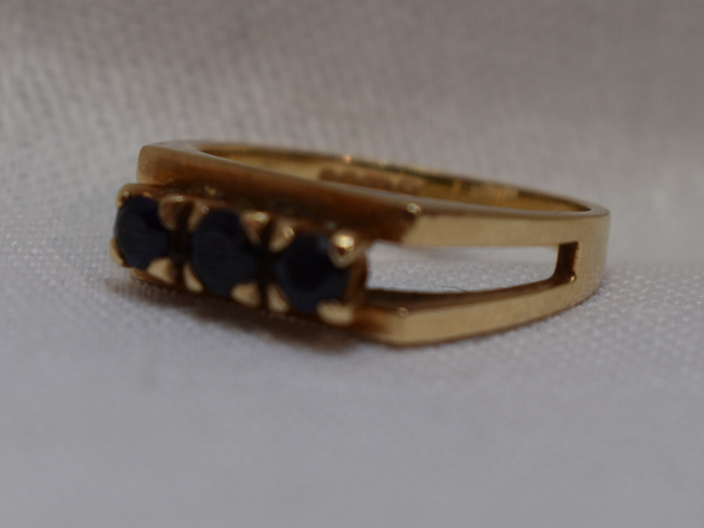 Lot 31 - A lady's dress ring having a trio of sapphires in claw set mount to open shoulders on a 9ct gold