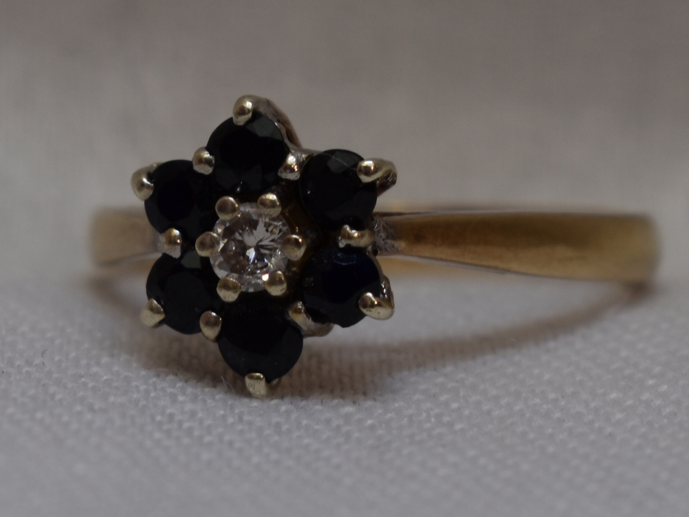 Lot 33 - A lady's dress ring having a diamond and sapphire cluster in claw set basket mount on a 9ct gold