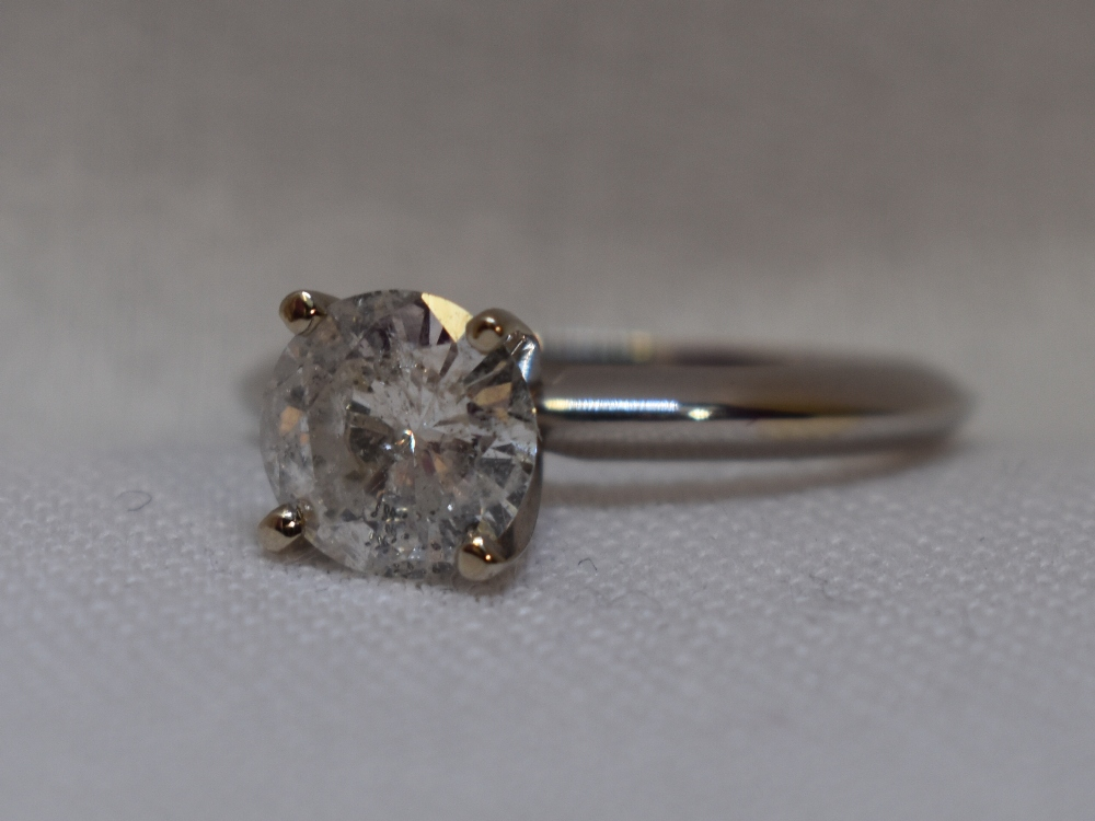Lot 50 - A lady's diamond solitaire dress ring, approx 1.1ct in a 4 claw raised mount on a white metal loop