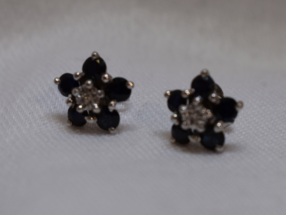 Lot 54 - A pair of diamond and sapphire daisy cluster stud earrings in 9ct white gold mounts