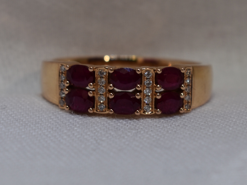 Lot 44 - A lady's dress ring of band form having six oval rubies interspersed by rows of diamond chips on a