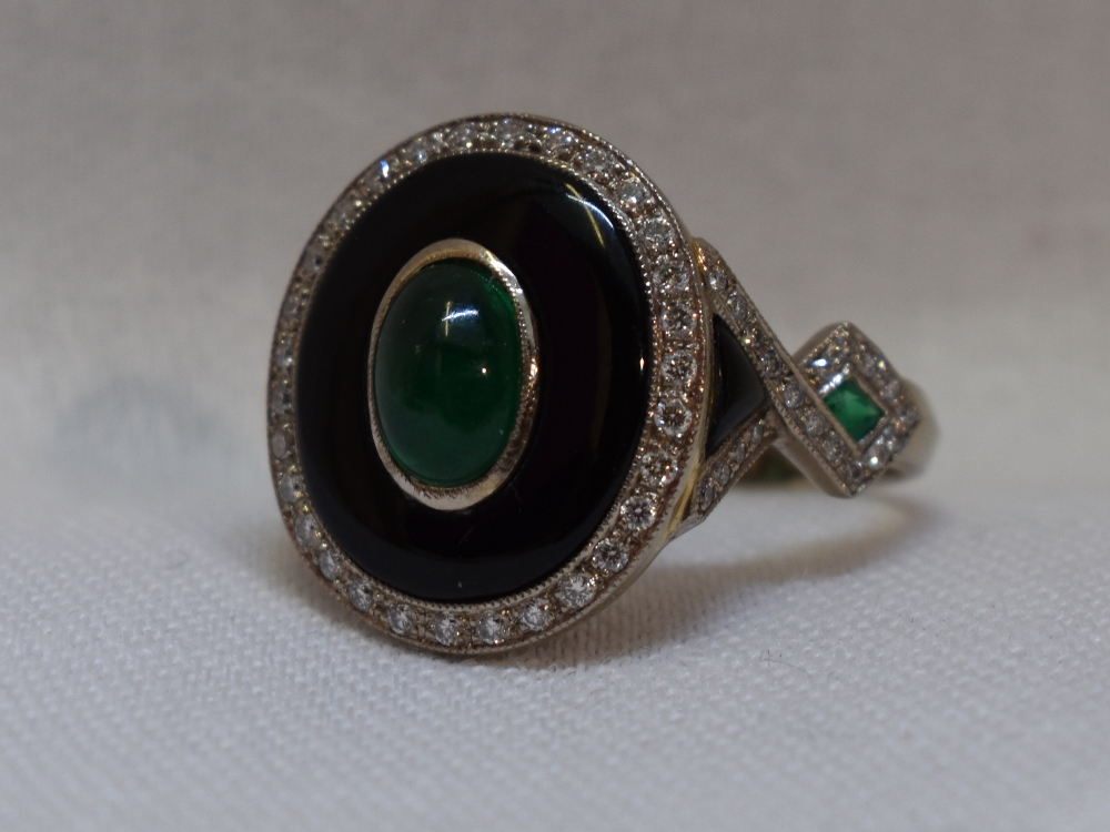 Lot 45 - A lady's dress ring having a central emerald cabouchon in a black enamelled mount with diamond