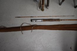 A three peice 10ft split cane fly rod with spare tip in canvas sleeve