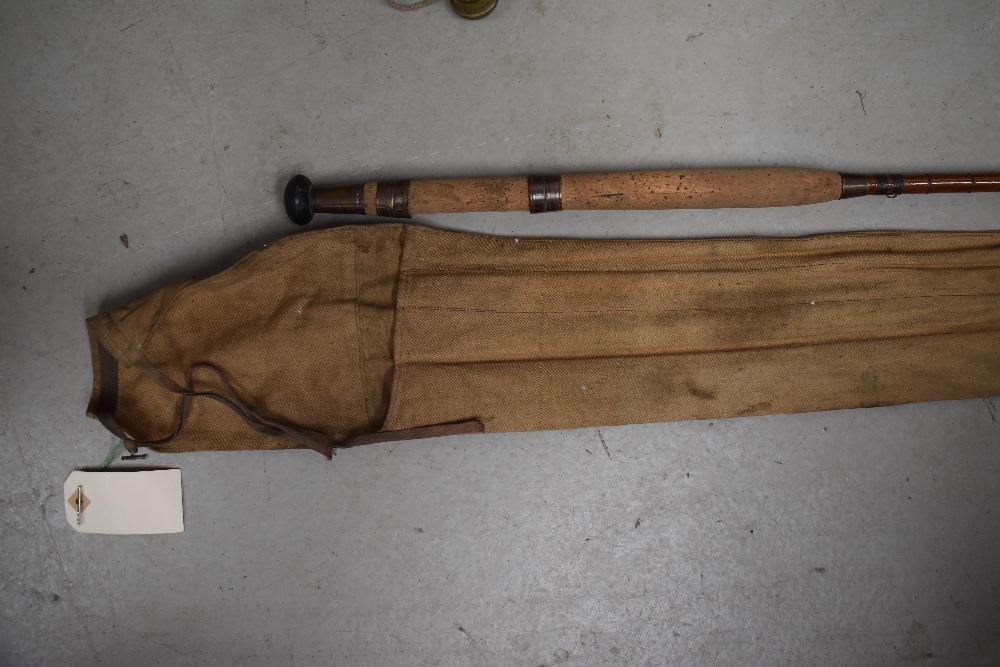 Lot 383 - A vintage cane fishing rod approx 11ft unmarked with sleeve