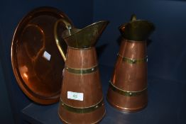 Two copper and brass pitchers and a copper charger.