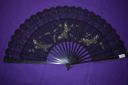 A black gauze and lace fan, circa 1890, with painted butterflies and trimmed with sequins having