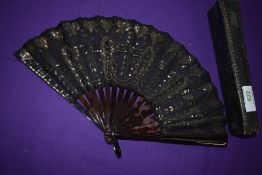 A late 19th century silver spangled black gauze fan with tortoiseshell ribs , in silk lined box.