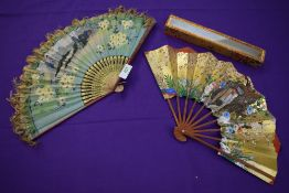 Two oriental hand painted paper fans, one having fringing to edge and both with wooden ribs.