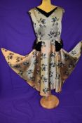 A vintage 1950s gold dress with flocked pattern and black velvet detailing to neckline and skirt,