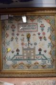 A framed cross stitch sampler by Annie Akister, aged 11 1885, depicting a castle, animals and floral