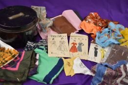 A metal sailors hat tin containing an assortment of 50s dress patterns, stockings,scarves and